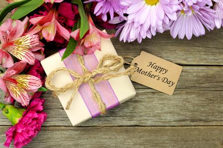 madera r�stica: Frontera de flores con caja de regalo y etiqueta Feliz D�a de las Madres en contra de un fondo de madera r�stica Foto de archivo
