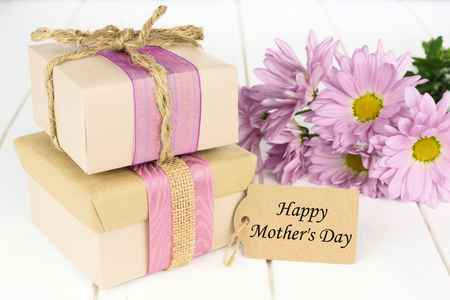 Handmade gift boxes with Happy Mothers Day tag on white wood with flowers Stock Photo
