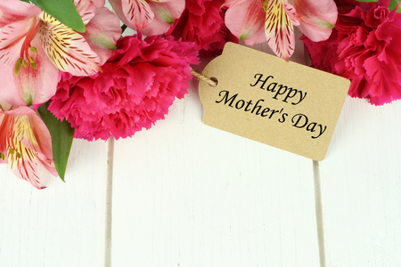 Happy Mothers Day gift tag amongst top border of pink carnation and lily flowers against white wood background