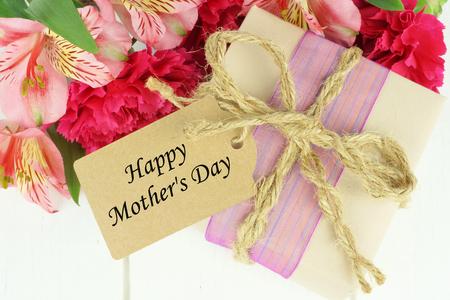 해피 어머니의 날 태그와 핑크 카네이션과 흰색 나무 배경에 대해 백합 꽃과 선물 상자
