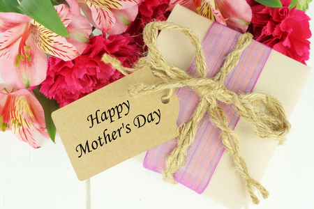Gift box with Happy Mothers Day tag and pink carnation and lily flowers against white wood background