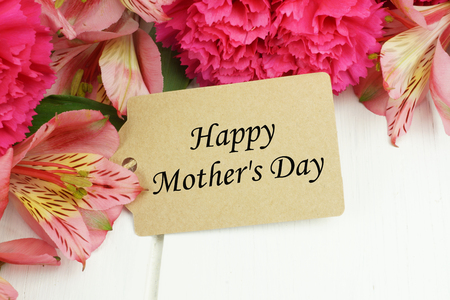 Happy Mothers Day gift tag close up with pink carnation and lily flowers against white wood background