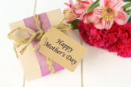 白い木製の背景の幸せな母の日のタグとピンク カーネーションとユリ花とギフト ボックス 写真素材