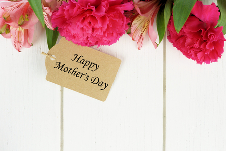 Happy Mothers Day gift tag amongst pink carnation and lily flowers against white wood background