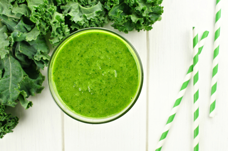 green: Green smoothie in a glass with kale overhead view on white wood