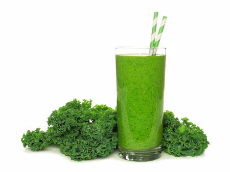 jugos: Batido verde sana con la col rizada en un vaso con pajitas aislado en un fondo blanco Foto de archivo
