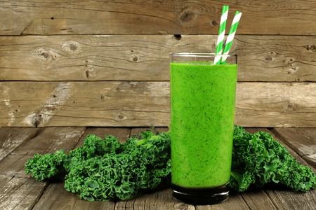 green: Healthy green smoothie with kale in a glass against a rustic wood background