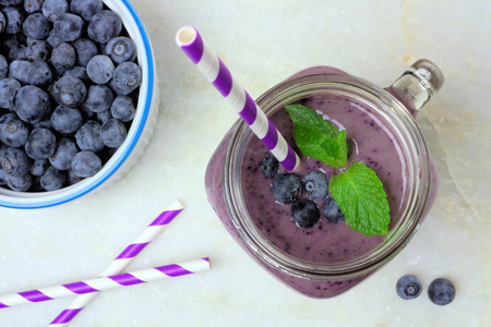 Blueberry smoothie with mint in mason jar glass with straw. Above view on white marble.