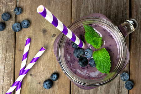 straw: Blueberry smoothie with mint in mason jar mug with straw. Overhead view on wood.