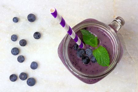 Blueberry smoothie with mint in mason jar glass with straw. Above view on white marble