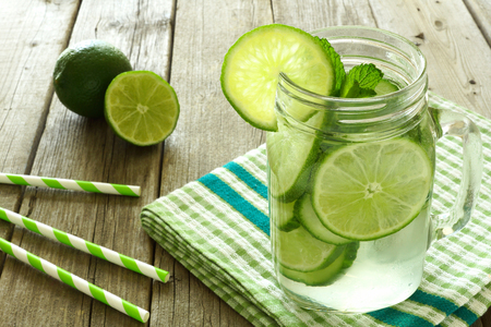 Detox water with lime and cucumbers in a mason jar on a wood table with checkered cloth and straws