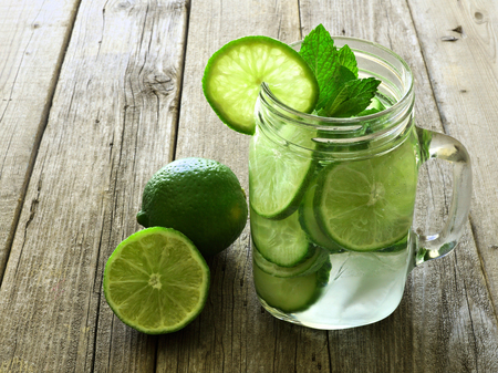 Detox water with lime and cucumbers in a mason jar against a rustic wood background