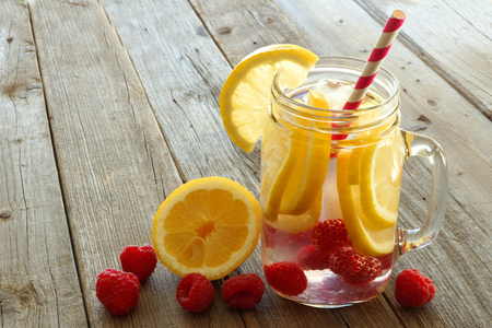 sliced fruit: Vitamin water with lemon and raspberries in a jar with straw against a wood background