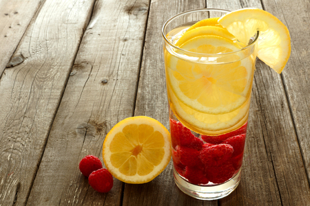 Nutritious fruit water with lemon and raspberries in a glass against a wood background