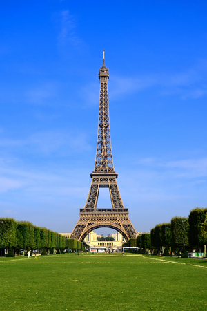 champ: View of the iconic Paris landmark the Eiffel Tower from Champ de Mars with vibrant blue sky France