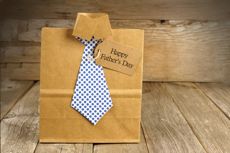 Fathers Day handmade shirt and tie gift bag with greeting card on a wood background