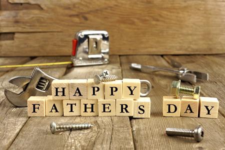 padres: Feliz Día de los Padres bloques con herramientas en un fondo de madera rústica Foto de archivo
