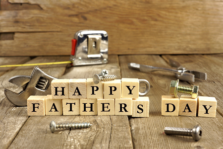 celebration day: Happy Fathers Day blocks with tools on a rustic wood background