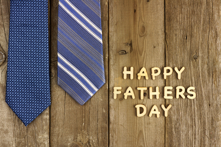 Happy Fathers Day wooden letters on a rustic wooden background with blue ties