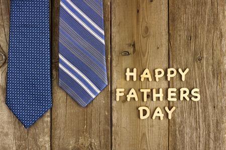 lazo regalo: Padres feliz letras de madera del día sobre un fondo de madera rústica con lazos azules