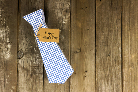 Fathers Day handmade tie shaped gift box with tag on a rustic wood background