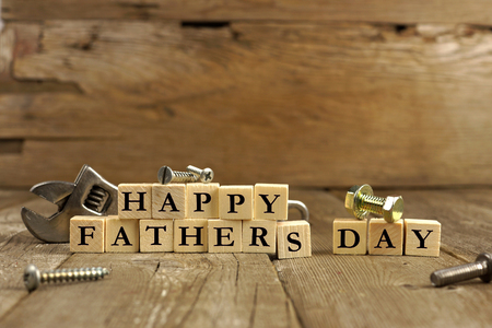 happy holidays text: Happy Fathers Day blocks with tools on a rustic wood background