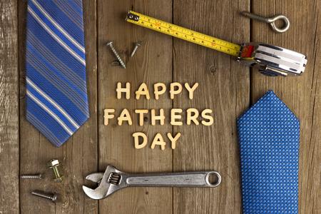ツールとネクタイのフレームで素朴な木製の背景にハッピー父の日の木の手紙