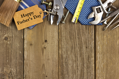 Día de padres feliz etiqueta de regalo con el borde superior de las herramientas y los lazos en un fondo de madera rústica Foto de archivo - 39565444