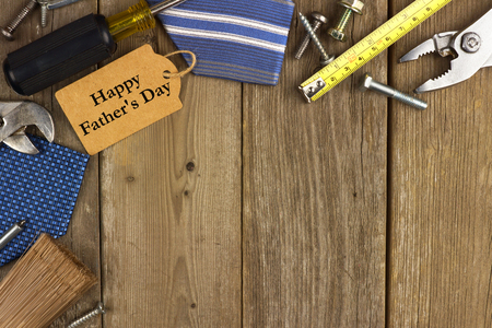 Happy Fathers Day gift tag with corner border of tools and ties on a rustic wood background
