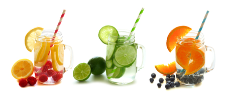 Three types of healthy detox water with fruit in mason jars isolated on a white background photo