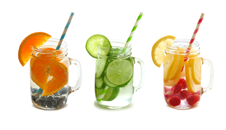Three types of fruit filled detox water in mason jars with straws isolated on a white background photo