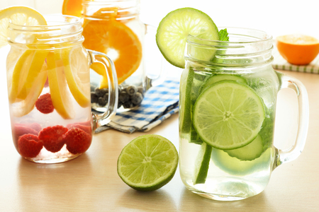 Detox water with various types of fresh fruit and vegetables in mason jars on a table photo
