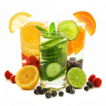 sliced fruit: Group of three glasses of healthy detox water with fresh fruit over a white background