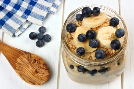 overnight: Blueberry and banana breakfast overnight oatmeal in a mason jar with spoon on white wood