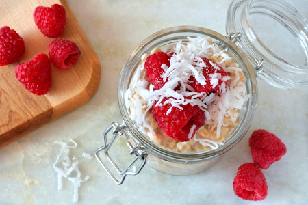 overnight: Healthy breakfast refrigerator oatmeal with fresh raspberries and shredded coconut in a glass jar downward view on white granite Stock Photo