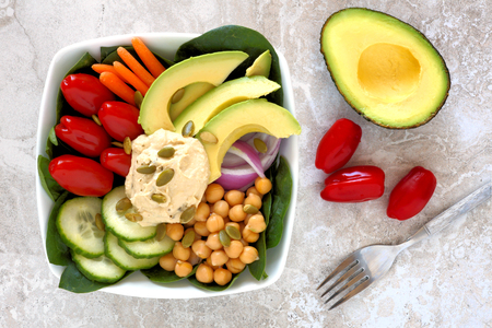 Healthy nourishment bowl with avocado hummus and mixed vegetables overhead scene on white marble Stock Photo