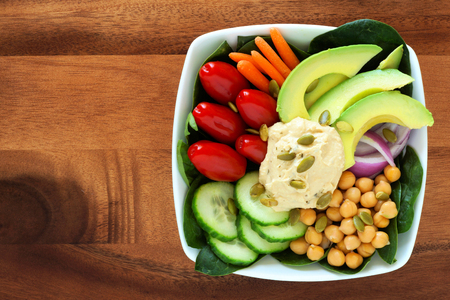 Nutritious lunch bowl with avocado hummus and mixed vegetables overhead view in square bowl on wood photo
