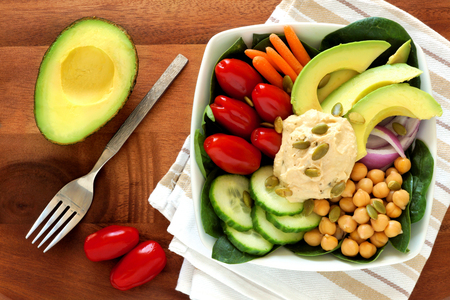 Healthy lunch bowl with avocado hummus and fresh vegetables overhead scene on wooden table photo