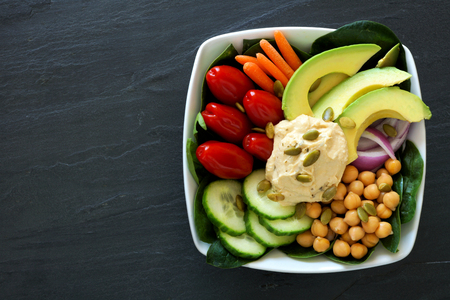 Healthy nourishment bowl with superfoods and fresh mixed vegetables overhead view on dark slate photo