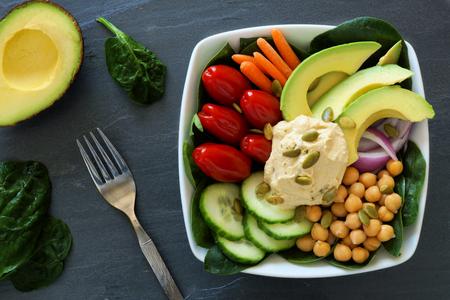 Ciotola Pranzo sano con supercibi e verdure fresche miste di scena in testa su ardesia scuro