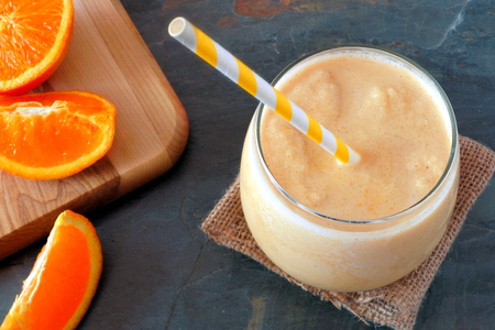 Healthy orange smoothie in a glass with striped straw and fresh fruit slices downward view on slate Stock Photo