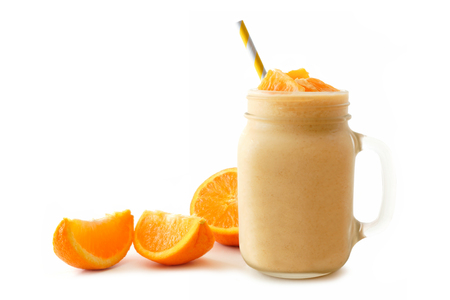 Orange smoothie in a mason jar glass with striped straw and fresh fruit slices isolated on white