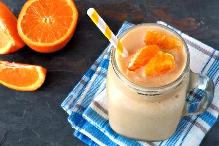 naranja: Batido de fruta de naranja en un albañil frasco de vidrio que descansa sobre tela facturado con rodajas de naranjas frescas sobre un fondo de pizarra