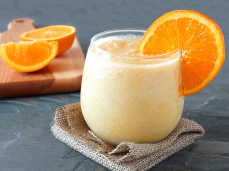Gesunde orange Frucht-Smoothie in einem stemless Glas ruht auf Sackleinen Tuch mit frischen Orangenscheiben im Hintergrund Standard-Bild - 39908024