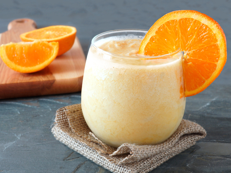 Healthy orange fruit smoothie in a stemless glass resting on burlap cloth with fresh orange slices in background