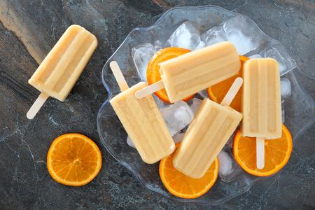 paletas de hielo: Paletas de helado de naranja yogur casero en un recipiente lleno de hielo con rodajas de fruta fresca contra un fondo de pizarra Foto de archivo