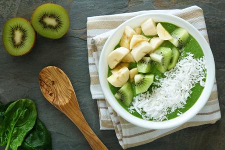 licuado de platano: Tazón de batido verde con plátanos espinacas kiwi fresco de frutas y coco sobre un fondo de pizarra