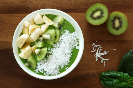 shredded coconut: Green smoothie bowl with spinach kiwi fruit bananas and shredded coconut on a wood background