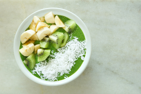 Green smoothie bowl with bananas fresh kiwi and shredded coconut on a white marble background Stock Photo