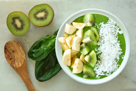 Green smoothie bowl with spinach bananas kiwi fruit and coconut with spoon on a white marble background Imagens